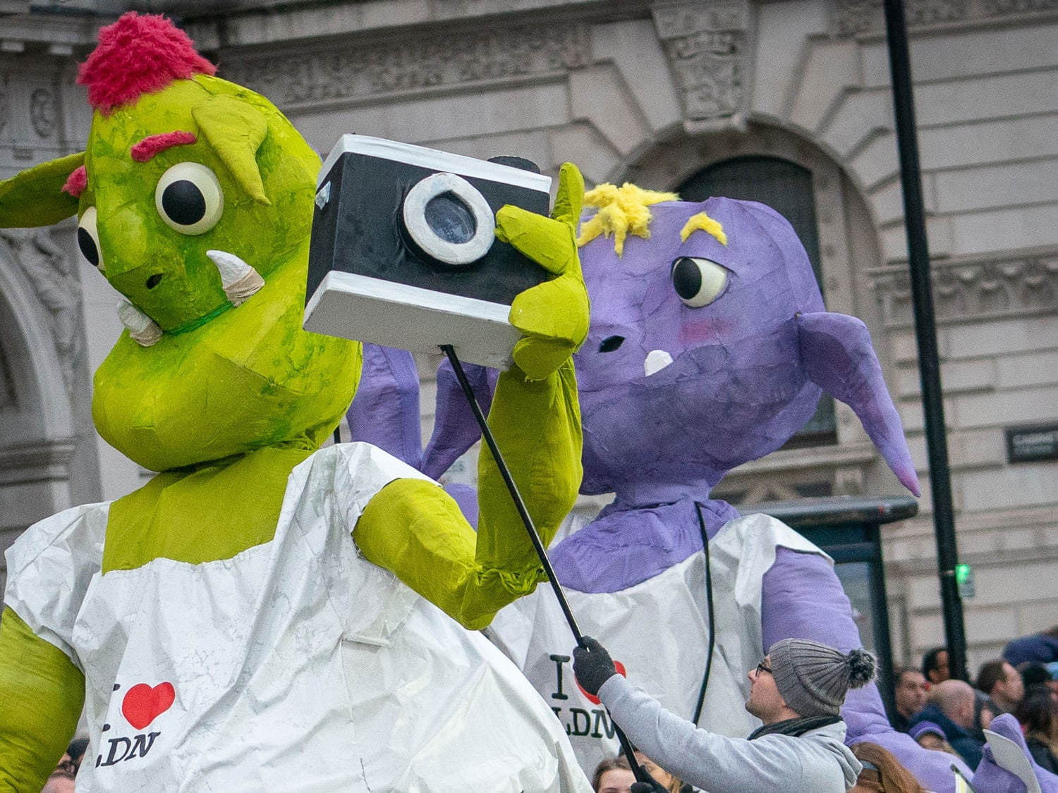 Two large alien puppets, one green and one purple.