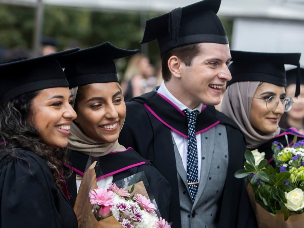 Graduates holding flowers and posing for a picture