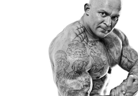 Black and white photograph of a bald man displaying his muscles and heavily tattooed torso.