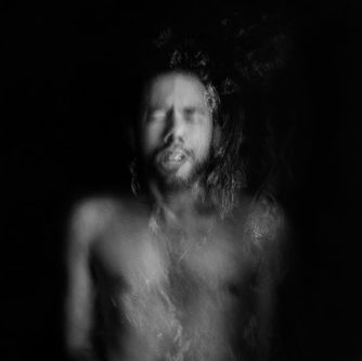 An out of focus black and white photograph of a topless man standing full-frontal, with his eyes closed.