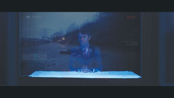 Still from The Drone - a man in a suit sits at a white desk, behind him is a countryside scene. The lighting is low and blue.