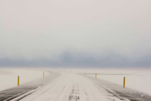 Photograph of a white, misty road leading into a horizon.