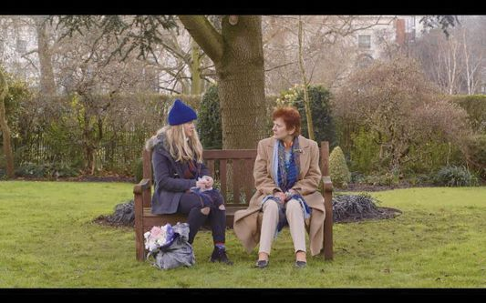 Still from A Rare Mutation - two women are sitting on a park bench having a conversation, in winter clothing.