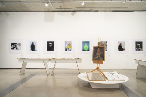 photographic portraits are displayed on gallery wall with tables in front showcasing more fashion imagery