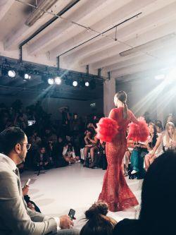 Model on catwalk wearing red dress.