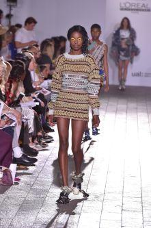 A model walking down a catwalk wearing a knitted dress