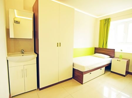 Cedars Hall Standard room (shared bathroom) including single bed, very large wardrobe, sink basin with mirror and desk
