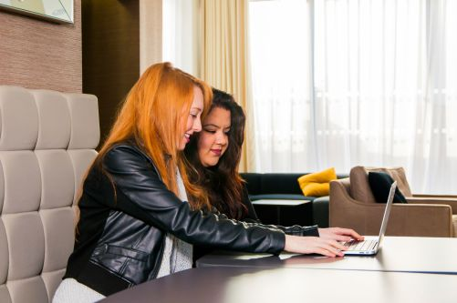 Photo of two female students working at a laptop in The Costume Store
