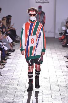 A model walking down a catwalk wearing a brightly striped garment, headband and sunglasses