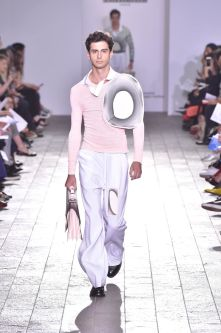 A model walking down a catwalk wearing a light pink top with very light purple trousers