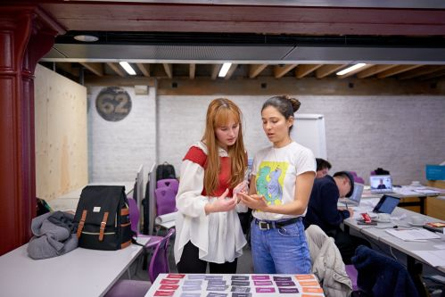 2 students having a discussion as they are holding a card