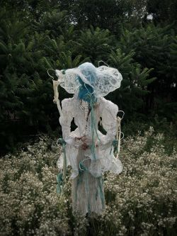 Handcrafted mannequin in meadow dressed in variety of fabrics.