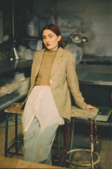Female model in tailoring, leaning on stalls