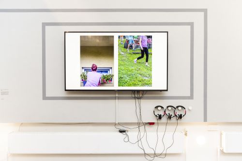 A screen with headphones showing a split-screen with people walking.
