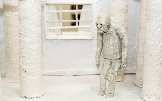 A figure of an old man standing slightly bent over. The materials that make up the scene are all white.