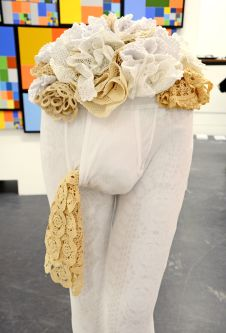 A mannequin wearing long johns stuffed with crocheted doilies