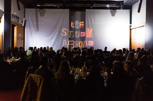 Room full of student, stage lit up with the words 'LCF Study Abroad'.
