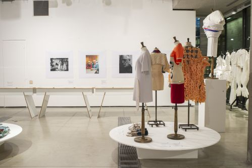 exhibition with mannequins and portrait photos on back wall