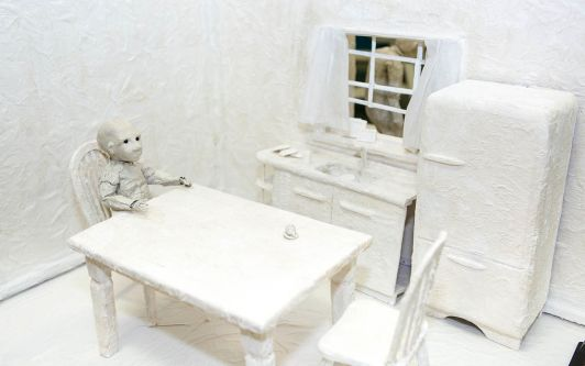 A small child sits at a kitchen table. The materials that make up the scene are all white.