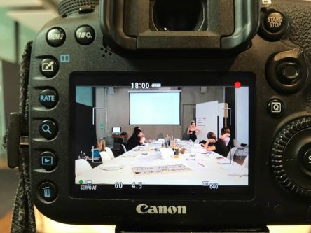 A photo of a camera taking a photo of a meeting room