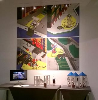 A series of four brightly coloured prints on a wall, below is an i-pad screen and small models of buildings