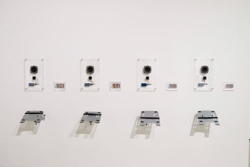An installation of four electronic devices on a white wall