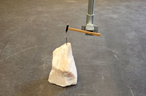 A hammer attached to a robotic arm tapping a nail into a crystal
