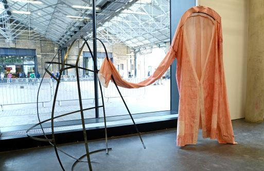 A garment hung up with an extremely long arm attached to a metal sculpture