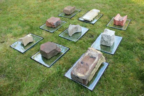 bricks and rocks laying on glass sheets on grass