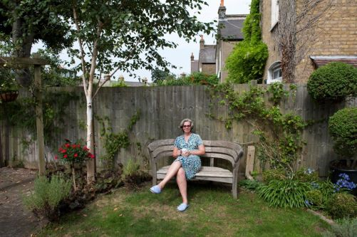 a woman sat on a bench in a garden