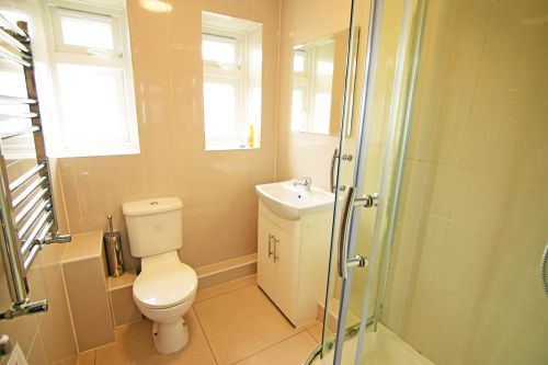 Shared bathroom at Cedars Hall, with shower, sink, toilet, mirror and heated towel rack