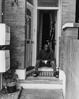 black and white photo of famioly standing on the doorstep of their home