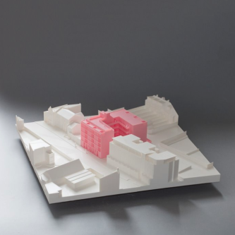 a 3D printed building model in pink surrounded by buildings in white