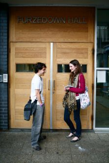 Photo of two students standing outside the entrance to Furzedown Student Village