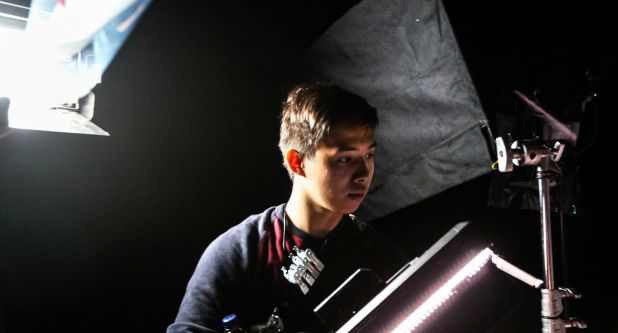 A student operating lights in the television studios at London College of Communication