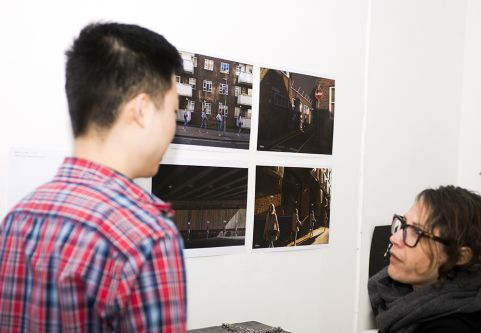 Two people in conversation in front of four pieces of student photography.