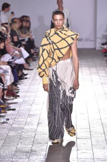 A model walking down a catwalk wearing an asymmetric top and grey and white detailed trousers