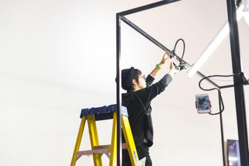 image of student standing on ladder installing camera on black frame