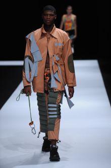 Male model wearing orange suit designed by Haochi Ma