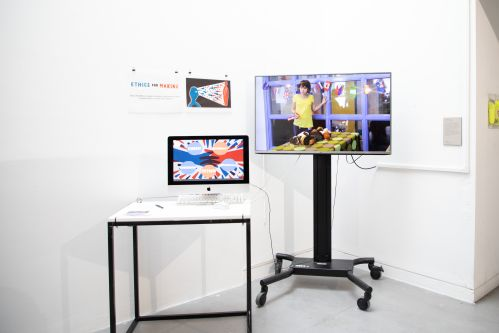 Installation shot of work by Gareth Johnson, using a large screen on floor stand and one macbook on a table.