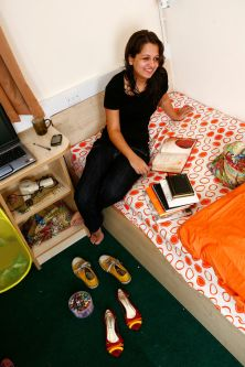 Photo of a female student sitting on a bed in Will Wyatt Court