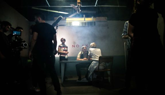 Students using sound, lighting and camera equipment to film a scene within London College of Communication's television studios