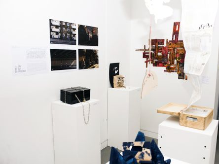 A wide shot of a white cube space featuring several plinths holding student work and additional pieces hung on the wall.