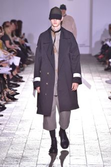 A model walks down a catwalk wearing a tailored navy coat over the top of a grey outfit. The model is also wearing a cap.