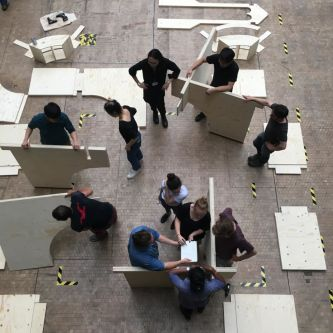 People constructing a model of Watts Chapel in The Street at Central Saint Martins