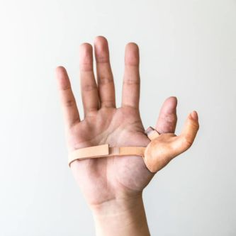 A hand with a prosthetic extra thumb