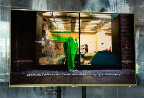 Image of screen showing film of person wrapped in green material