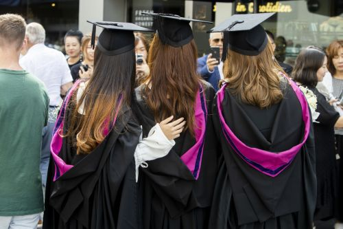 The back of three female graduates having a photograph taken