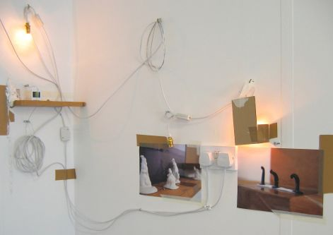 Installation piece featuring lights, photos and exposed wires by Arabella Finch.