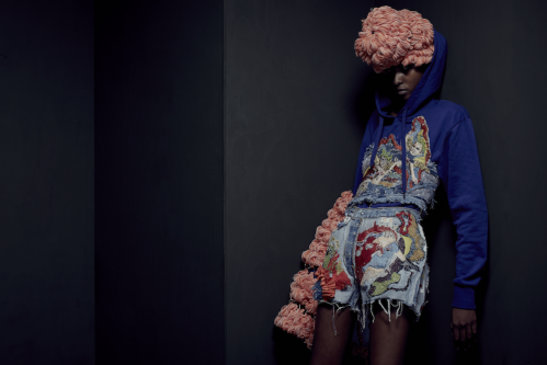 Model with woven pink headpiece and embroidered jumper and denim shorts